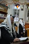 Jews praying in the synagogue with prayer shawl and phylacteries